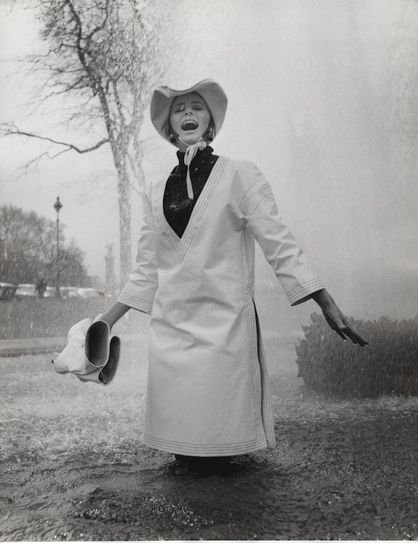 Jill Kennington wearing white PVC rain tunic and hat. Photograph by John Cowan 1963