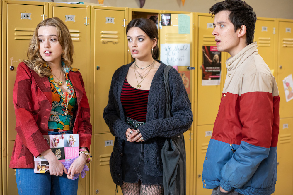 Aimee Lou Wood, Emma Mackey and Asa Butterfield in the Moordale High hallway